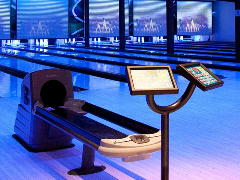 Ball return and bowling lanes lit in blue light