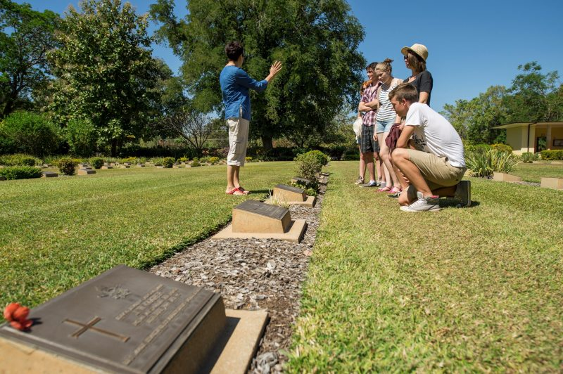 family standing over grave talking to tour guide