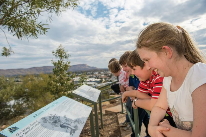 A group of kids read information signs on top of Anzac Hill in Alice Springs