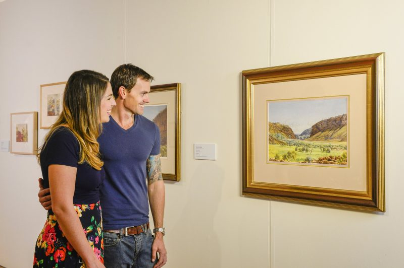 Man and woman looking at Namatjira watercolour painting
