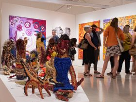 gallery with soft sculptures, aboriginal paintings in background and people looking at them