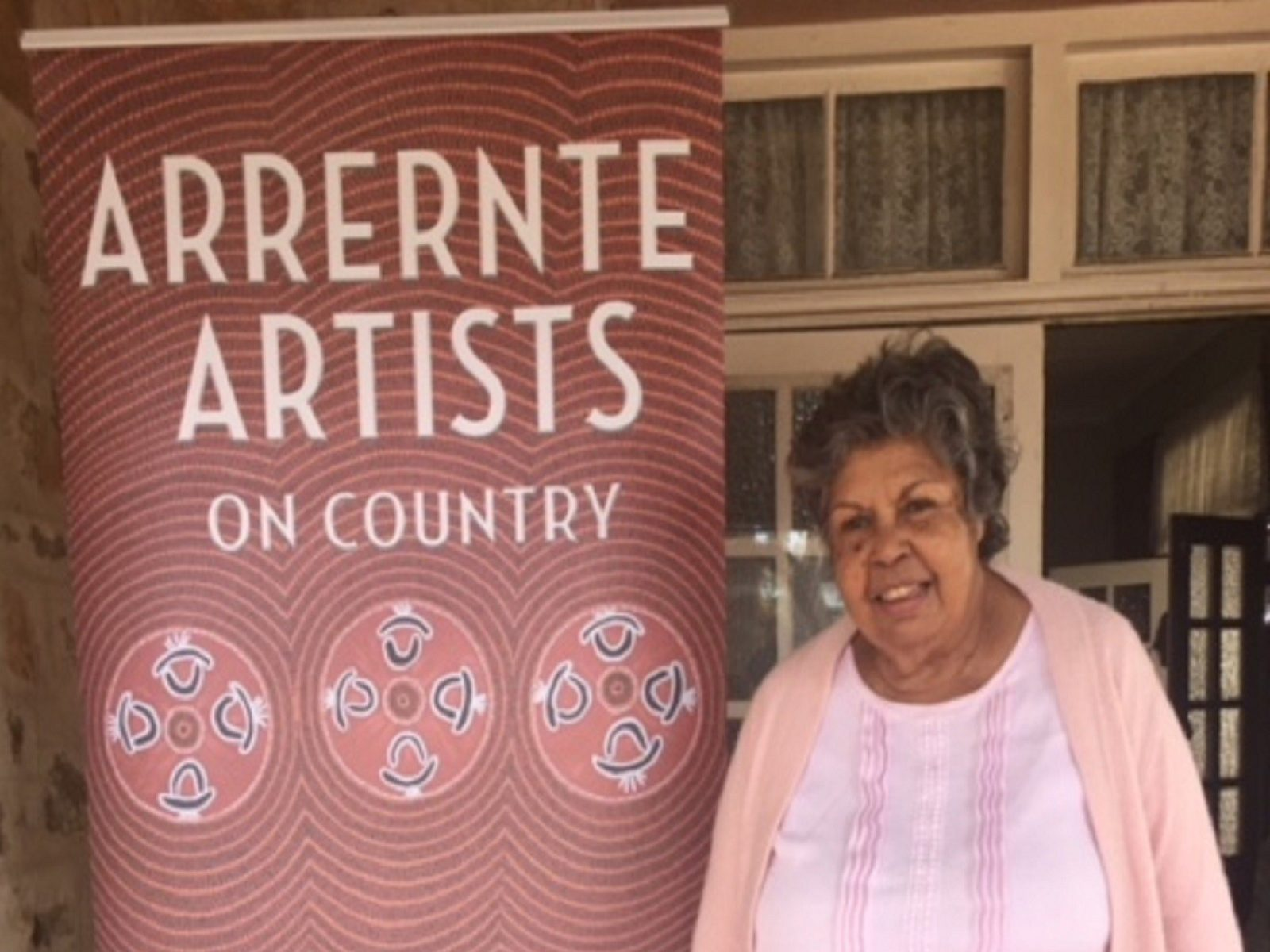 Pat Ansell Dodds with Arrernte Artist banner