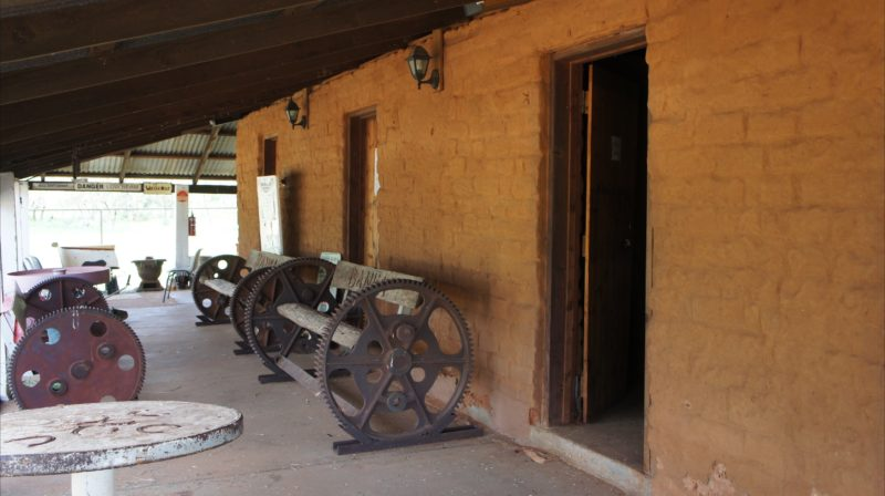 Verandah area of mud hut, with display of machinery parts