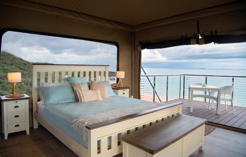 Glamping tent with large windows overlooking the beach