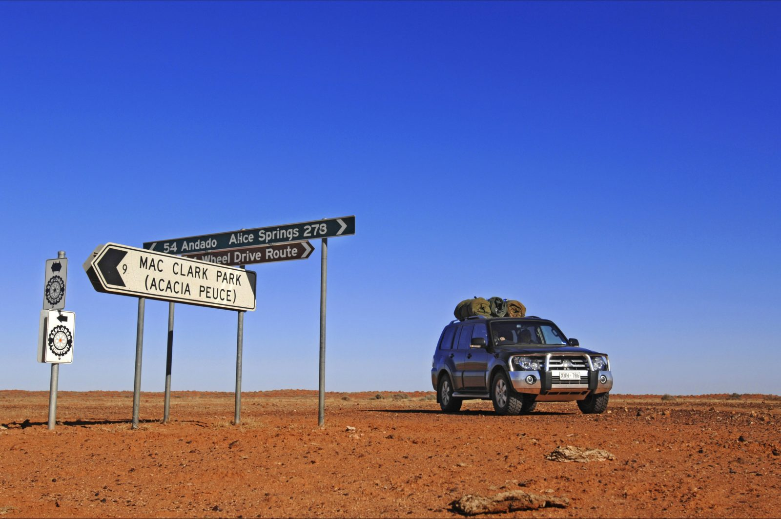 A four wheel drive near road signs on Bionns track in Simpson Desert