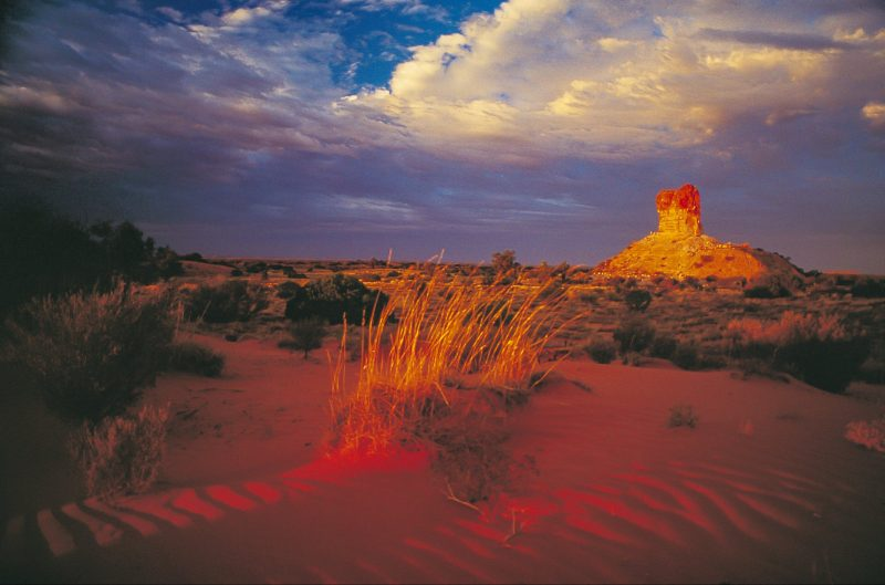 Chambers Pillar at sunset. The large sandstone column rises out of the red desert landscape.