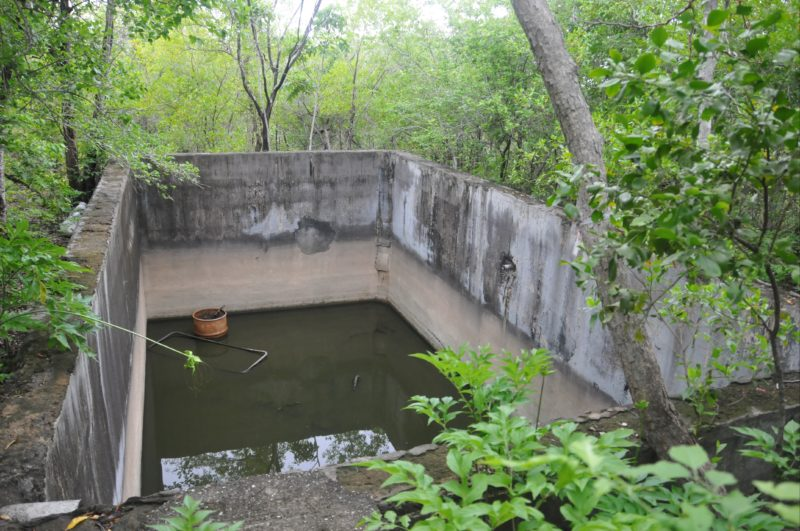 Concrete cistern. Adjacent are water tank slabs and remnants of a tank stand.