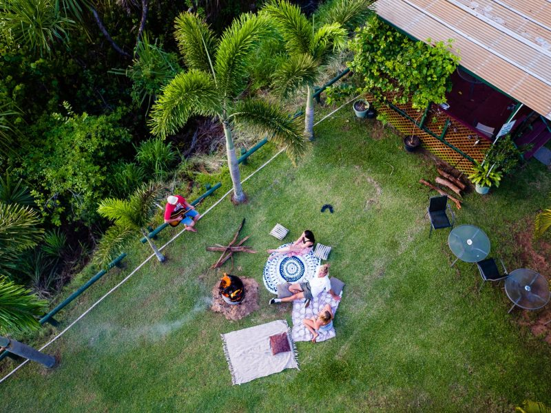 Aerial image of a family enjoying a picnic around the fire with a musician playing guitar