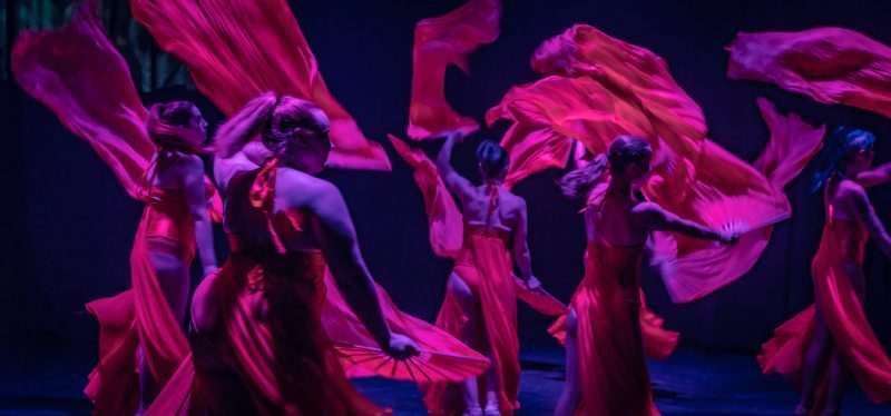 Performers dancing with red fabric during the Steam show in Brown's Mart Theatre.
