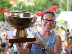 Lady holding laksa festival trophy