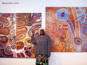 aboriginal artist standing in front of her work on canvas