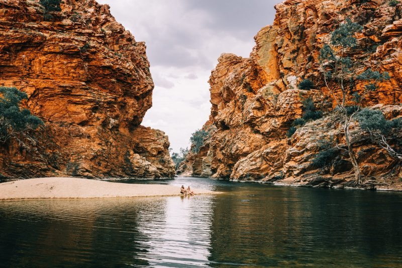 Two friends sitting on the banks of the waterhole with towering red escarpments in the background