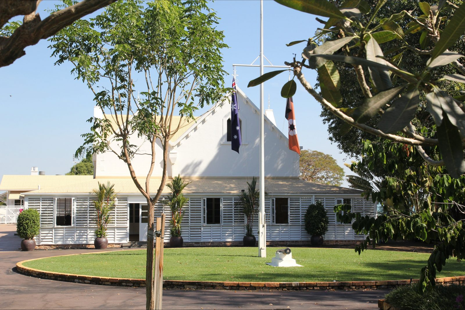 Front view of Government House with flag pole and frangipani tree in the foreground