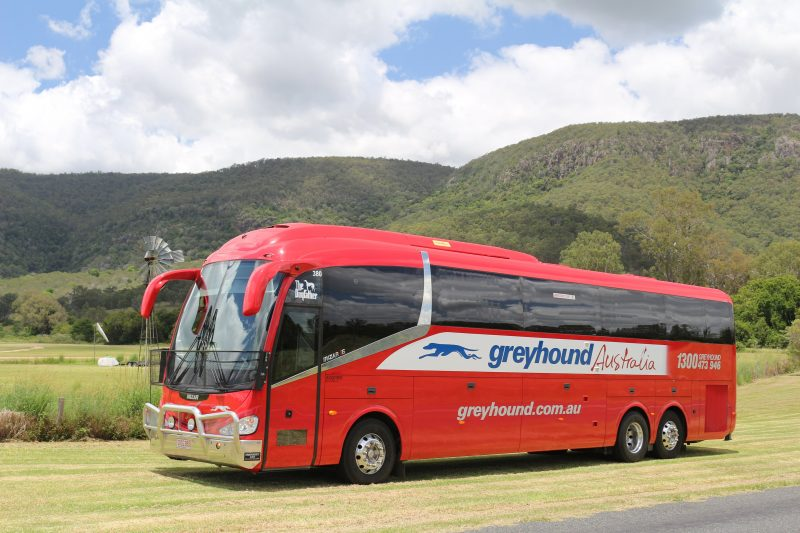 Greyhound coach in country side with windmill