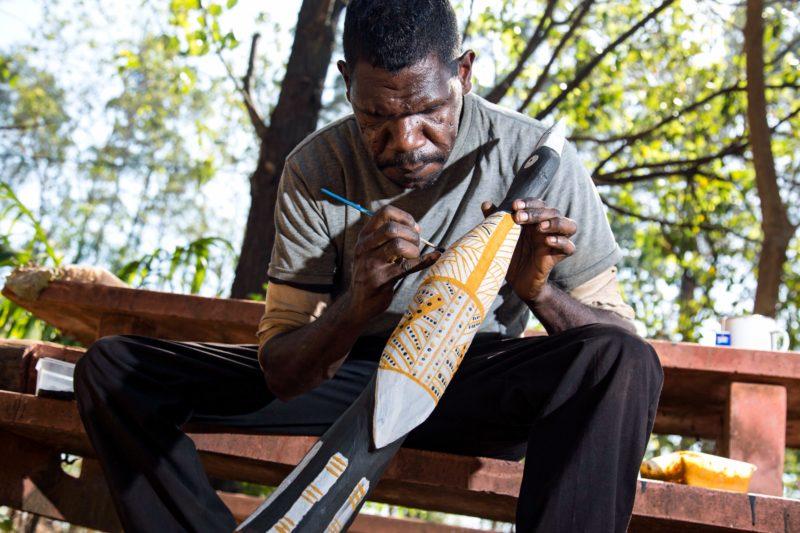 Jilamara artist member Gerry Mungtopi painting an ironwood carving with natural ochre