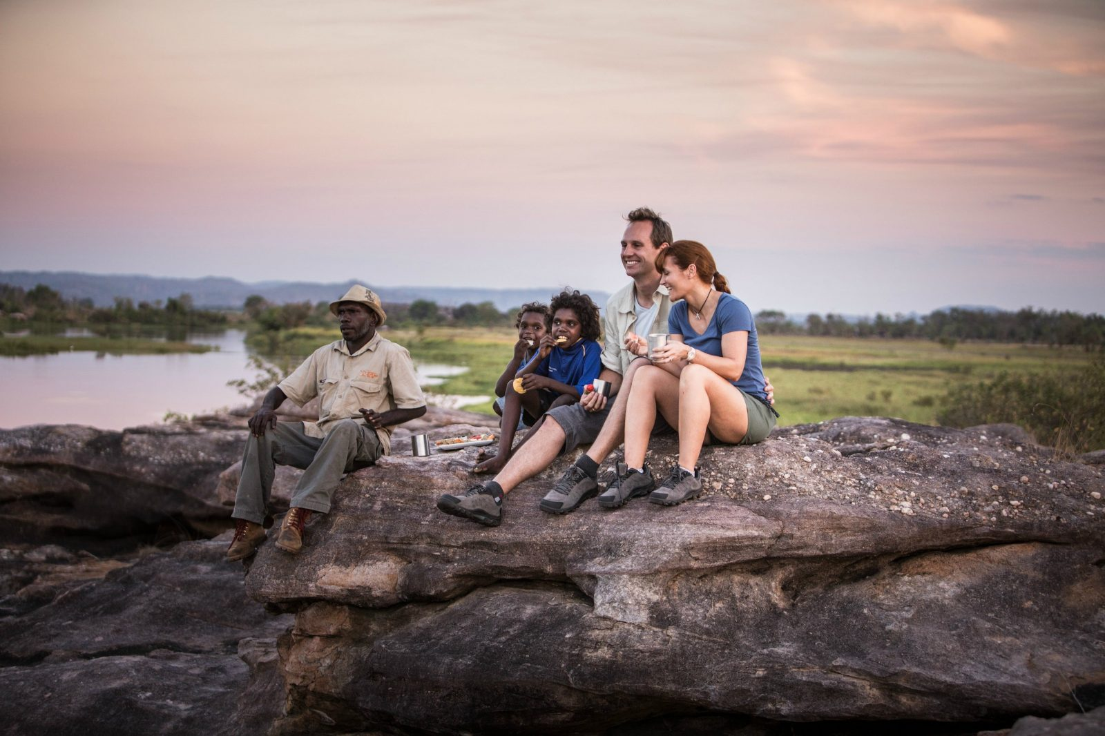 isitors looking over the Kakadu landscape with an Aboriginal guide.