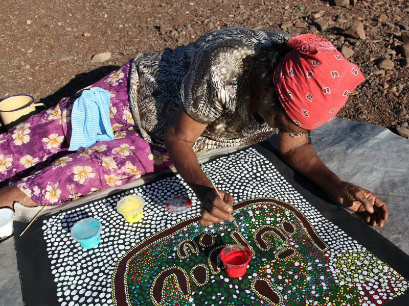 Artist, Pauline Ryan Nanaku, painting a children's story in the warm winter sun.