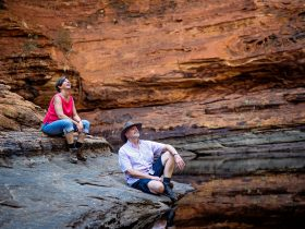 A Man and a Woman sitting by the Garden of Eden Waterhole on the Kings Canyon Rim Walk