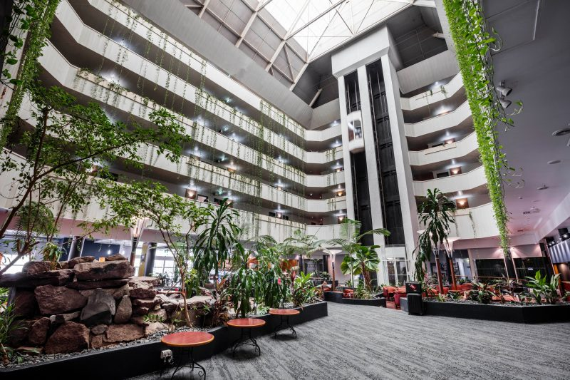 Hotel atrium with overhanging vines, tropical gardens & waterfall
