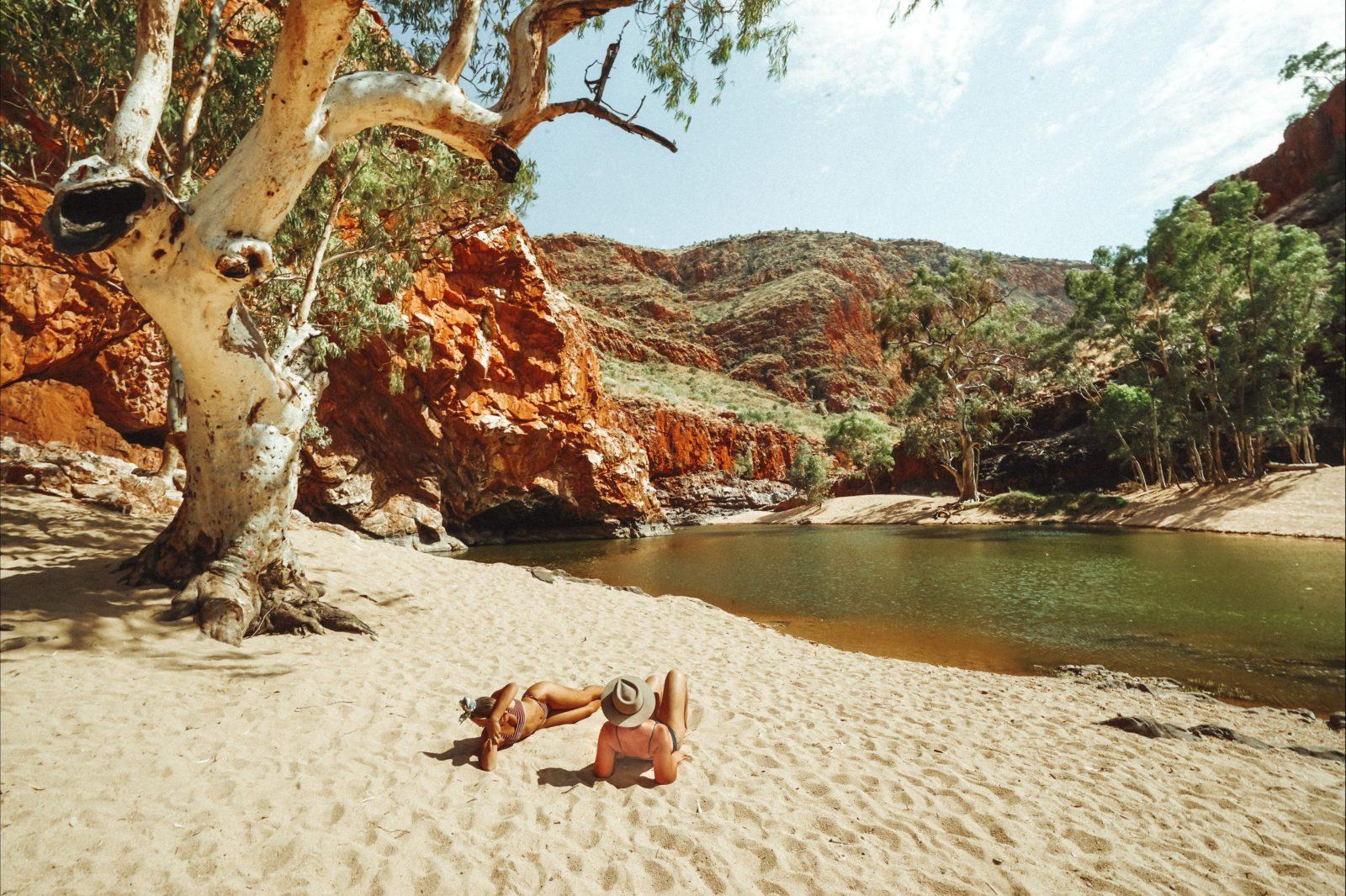 Two women sunbathing on white sand next to the waterhole at Ormiston Gorge