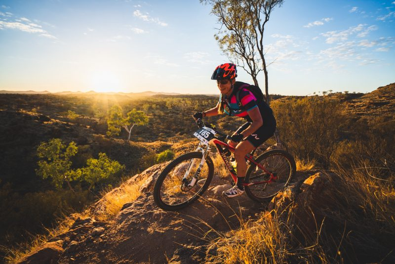 Woman reaching a peak of a hill with a stunning Alice Springs sunrise in the background