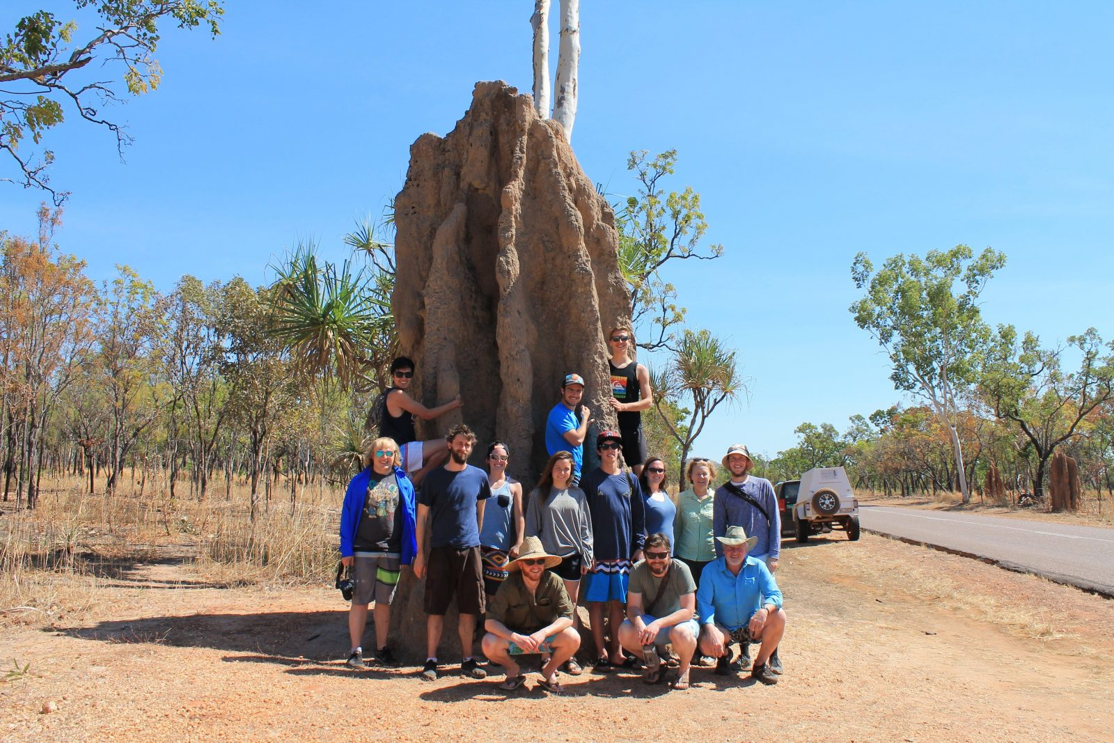 Group of people posing with a huge cathedral termite mound
