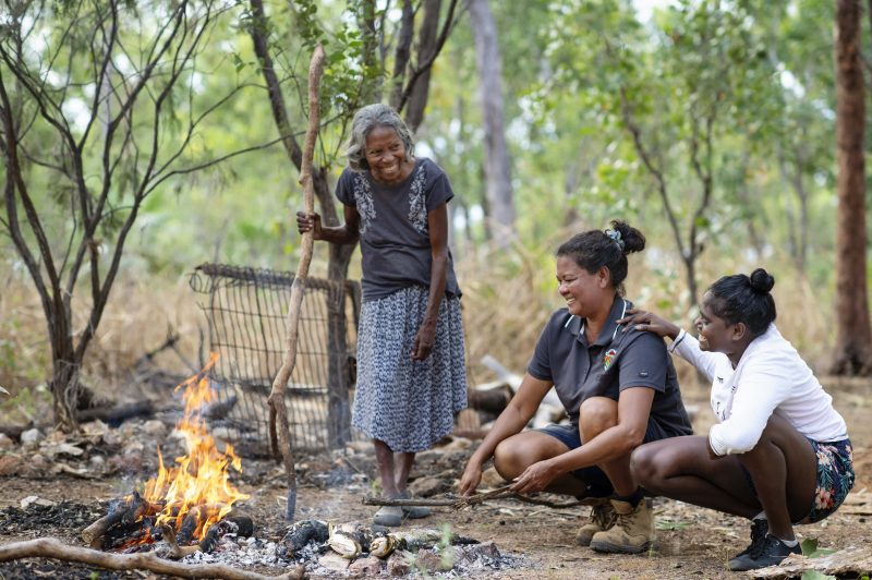 Indigenous women around a campfire.