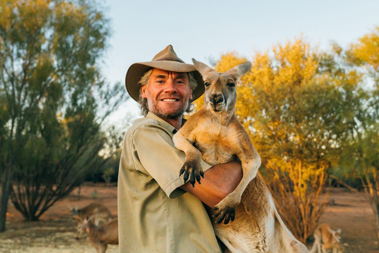 Chris Barns ('Brolga'), aka Kangaroo Dundee, cuddling a red kangaroo.