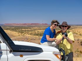 A couple taking photos from their 4WD at Tnorala/Gosse Bluff