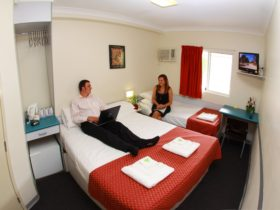 Value Inn Standard Room featuring 1Q and 1S bed. Rooms are compact and feature a TV, air conditioning, bar fridge, tea & coffee making facilities and ensuite.