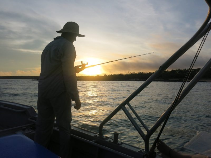 Guest fishing Barra fishing while watching the sunset.