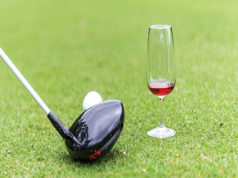 Golf club, ball and wine on green