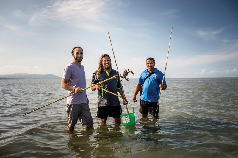 Aboriginal guide standing with guests in knee-deep water, holding spears and crab hunting.