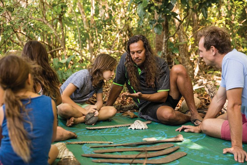 Aboriginal guide sitting with guests, showing Aboriginal tools and more.