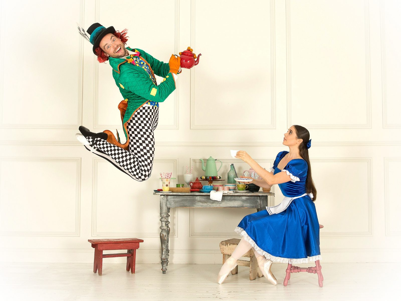 Alice sitting with tea while the Mad Hatter is Jumping mid-air