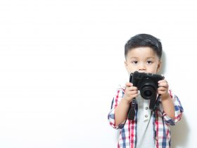 little boy with camera in hands, pointing at you