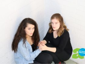 Two women are crouched in front of a white brick wall. They are holding hands and look scared.