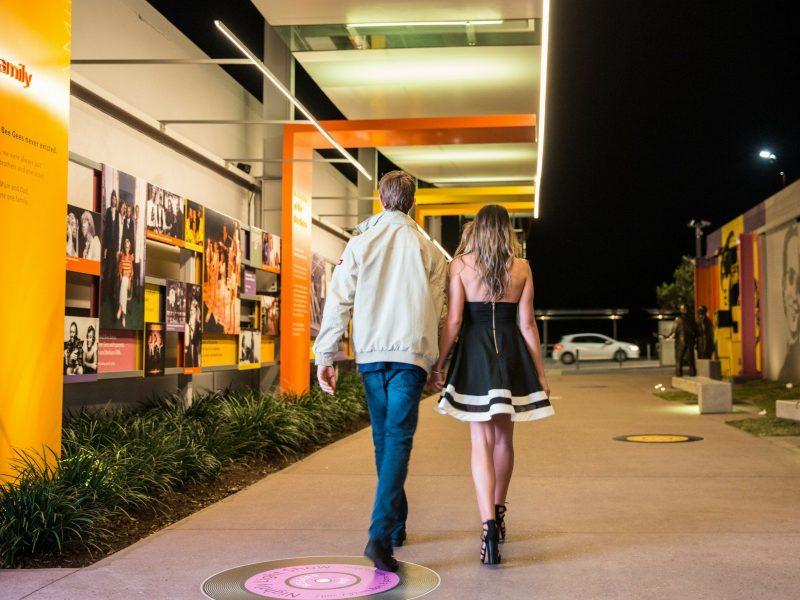 Couple walking down Bee Gees Way
