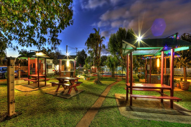 Barbecue Area in tranquil garden setting with covered picnic tables for guests comfort.