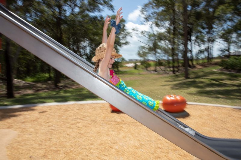 Young girl sliding down a metal slippery slide with her hands in the air