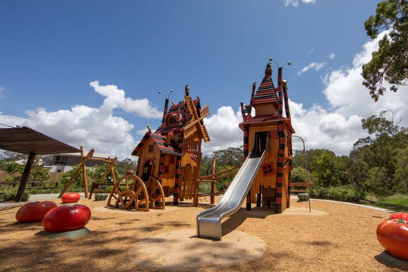 Two Halloween themed playground towers with a metal slide and a swing set on a gravel ground