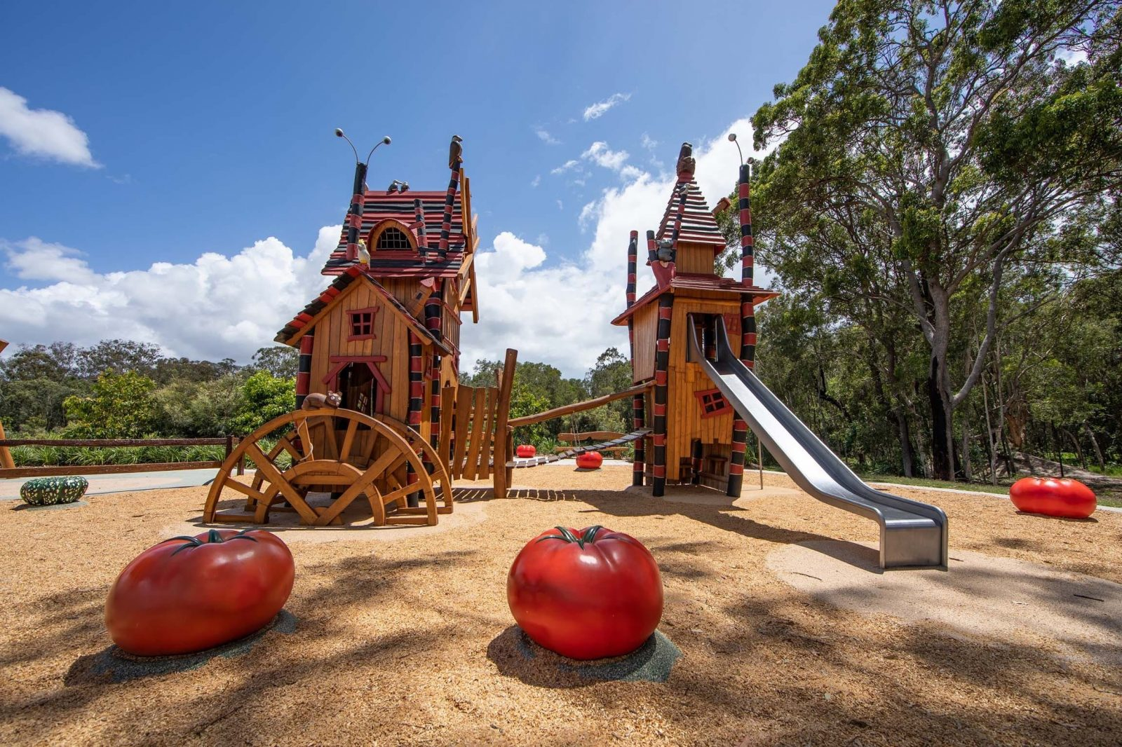 Two Halloween themed playground towers with a metal slide and two over sized tomatoes in foreground
