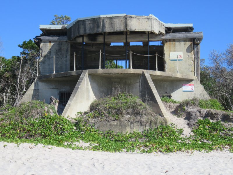 Concrete gun emplacement sits on sandy beach backed by coastal plants.