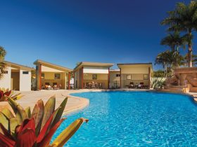 Brisbane Holiday Village's tropical lagoon pool with resort-style cabanas