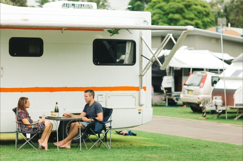 Couple drinking wine outside campervan