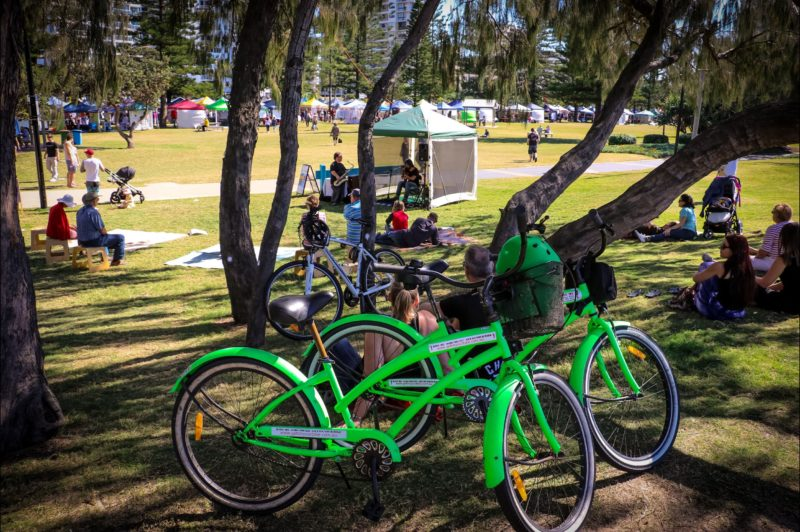 Two bright green hire bikes next to a shady spot at the Broadbeach Markets
