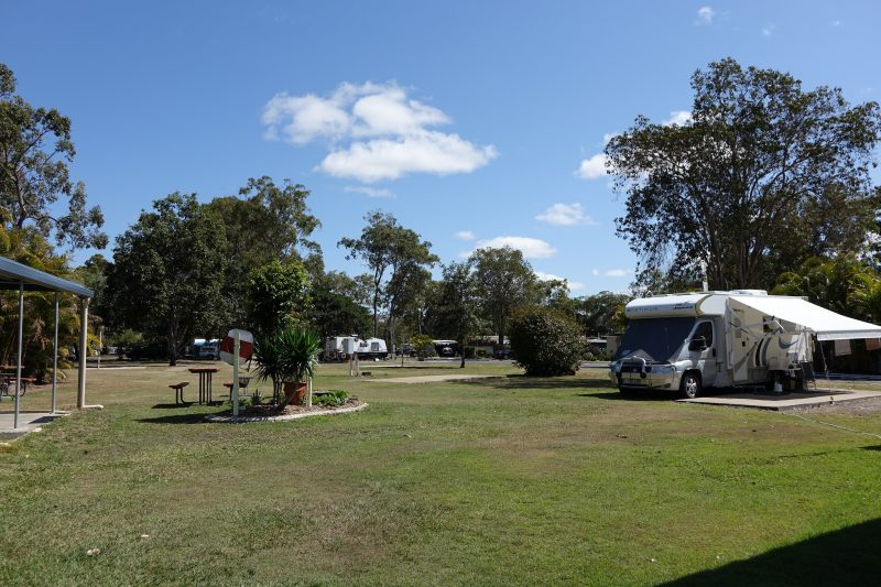 Image showing green lawns with a Recreational Vehicle parked beside a concrete slab.