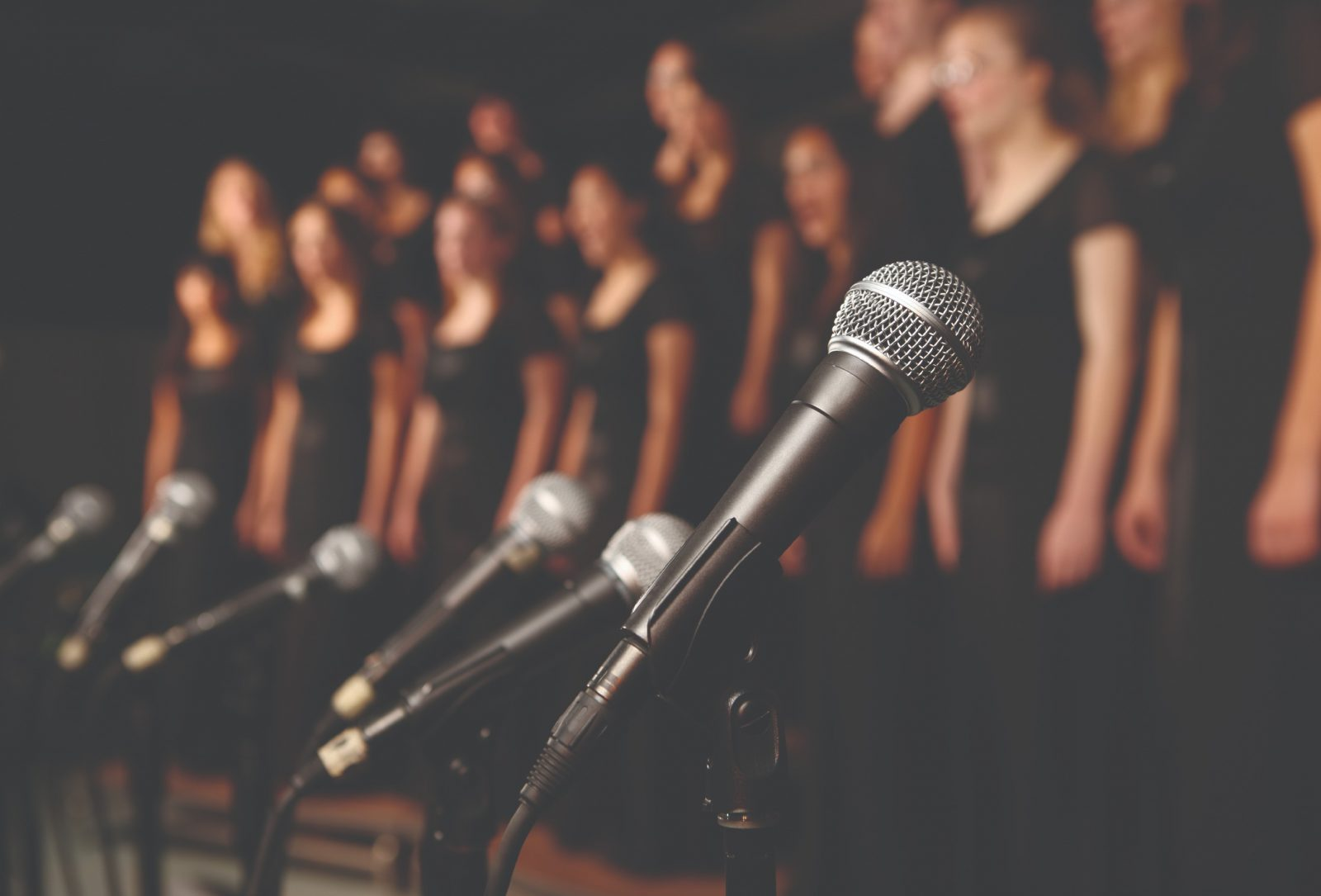 Stock image of a choir blurred into the background with microphones in the foreground