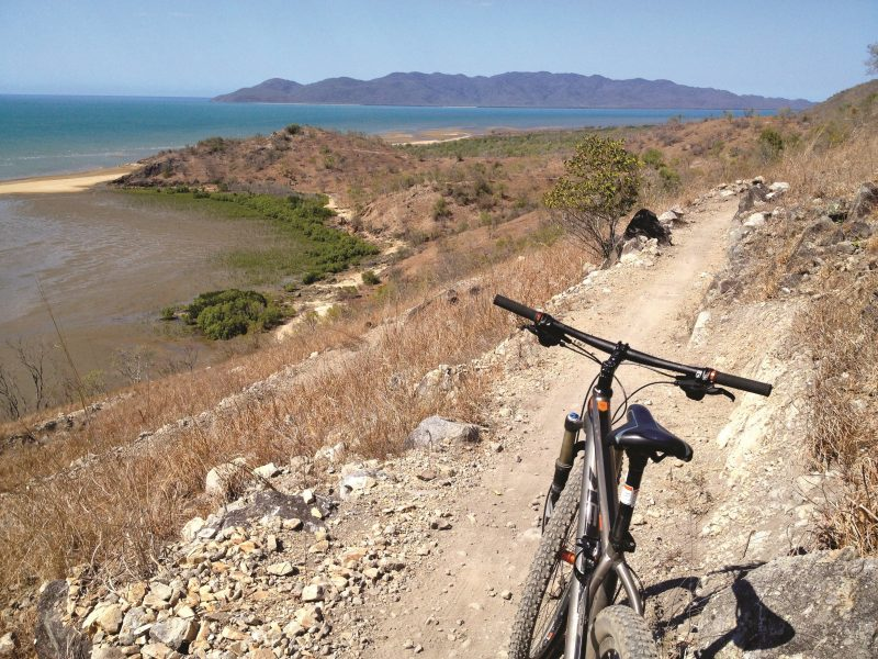 Mountain bike parked on dirt trail winding around a hill slope with a view over headland, ocean