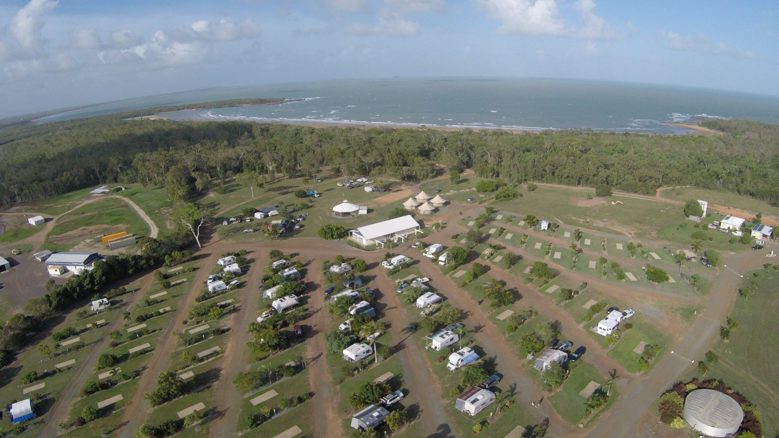 Aerial view of Park showing sites, amenities, glamping bungalow and the closeness of the beach